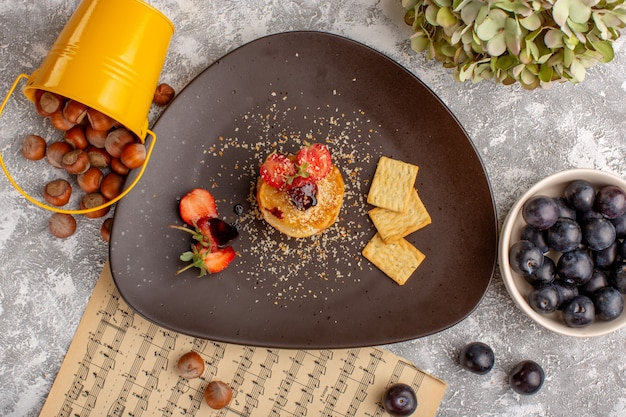 Top view salted chips designed with strawberries inside plate along with blackthorns on the white table, chips snack fruit berry