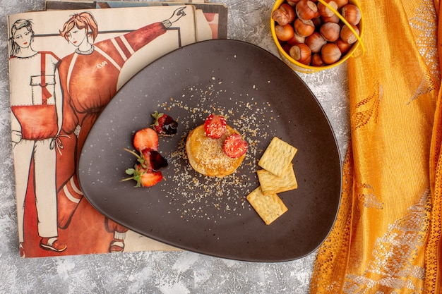 Top view salted chips designed with strawberries inside plate on the white table, chips snack fruit berry