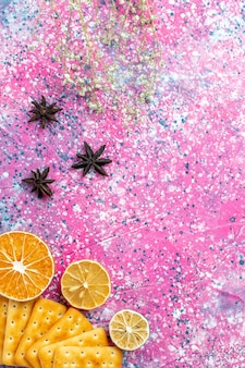 ピンクの机の上にレモンとトップビューの塩味のクラッカー