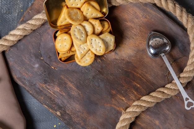 トップビュー塩味のクリスプクラッカー木製の机の上のロープにロープ灰色の背景クラッカークリスプスナック