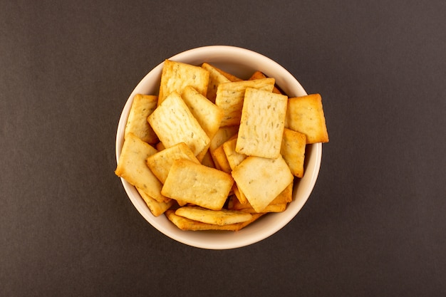 A top view salted crisps tasty crackers cheese inside white plate on the dark background snack salt crisp food