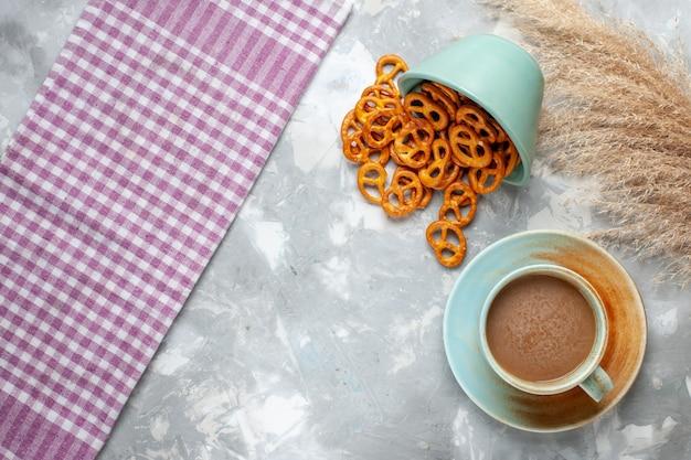 Vista dall'alto patatine salate con caffè al latte sullo sfondo chiaro bevanda crack sale snack foto