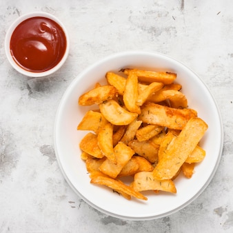 Top view of salted french fries on plate with ketchup