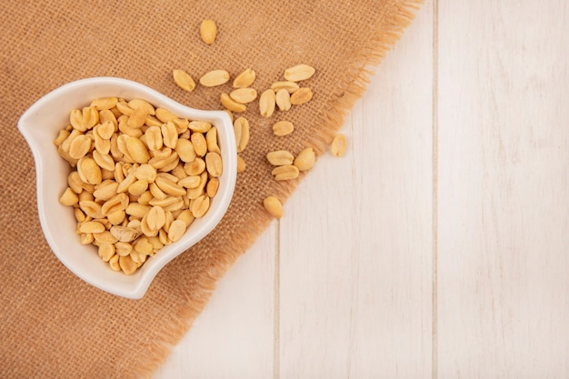 Top view of salty pine nuts on a bowl on a sack cloth on a beige wooden table with copy space