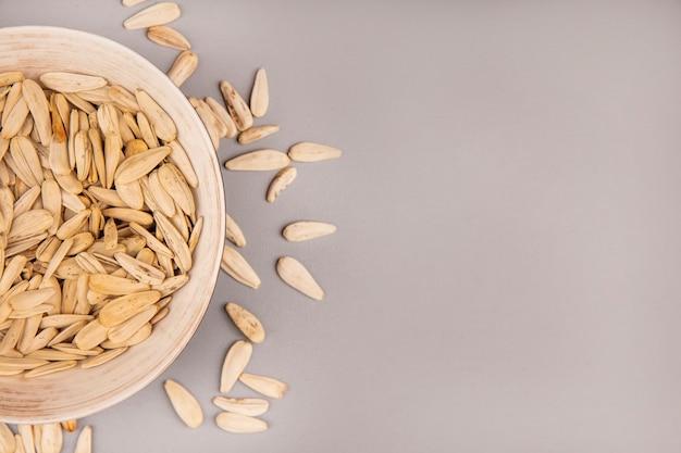Vista superiore dei semi di girasole bianchi salati su una ciotola con i semi di girasole isolati con lo spazio della copia