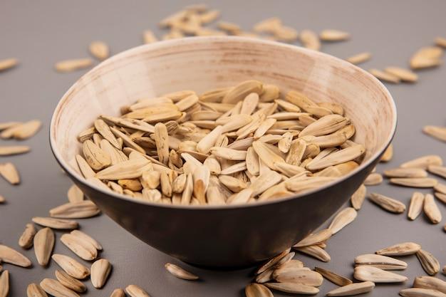 Vista dall'alto di semi di girasole bianchi salati su una ciotola con semi di girasole isolati