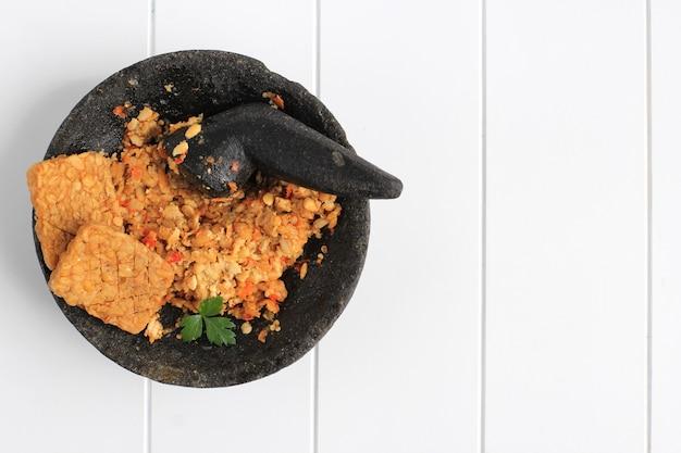 Вид сверху sambal tempeh, пряный измельченный tempe на каменном пестике. традиционные индонезийские блюда с острым и пикантным вкусом. копирование пространства на белом фоне деревянные