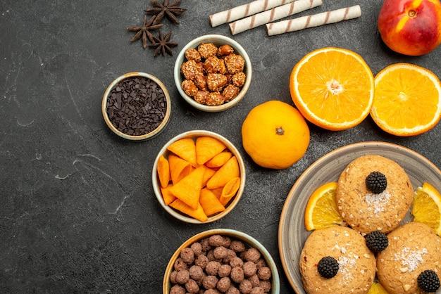 짙은 회색 표면의 달콤한 과일 비스킷 쿠키 차 케이크에 오렌지 조각이 있는 탑 뷰 샌드 쿠키