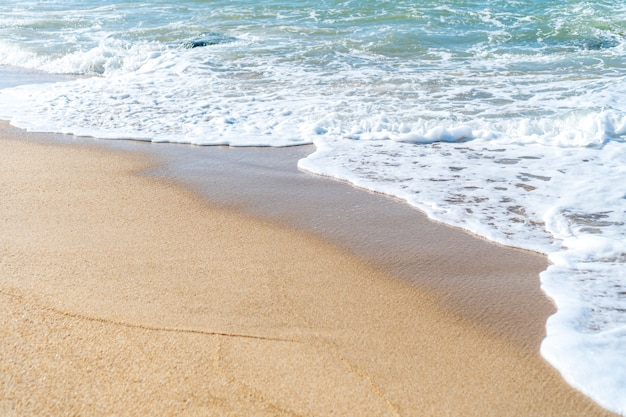 Top view of sand and water clean beach and white sand in summer with sun light blue sky and bokeh background.
