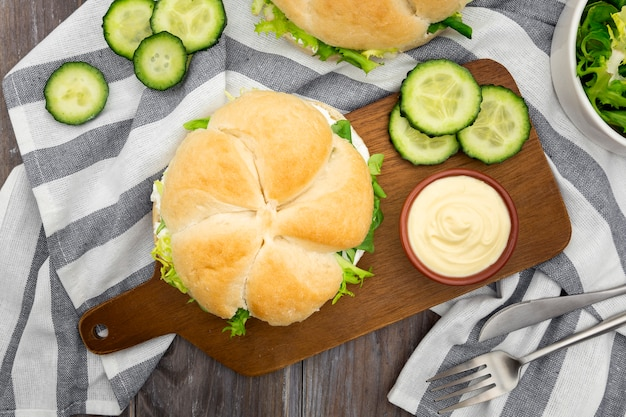 Top view of sandwich on chopping board with mayo and cucumber slices