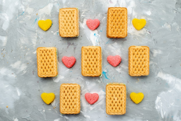 A top view sandwich cookies with colored heart shaped marmalades on the white desk cookie biscuit color