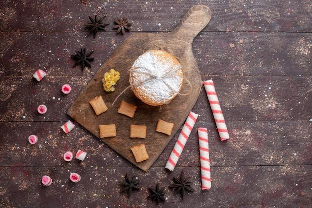 Вид сверху сэндвич-печенье со сливками вместе с леденцами на коричневом фоне, печенье, печенье, сладкие сахарные конфеты