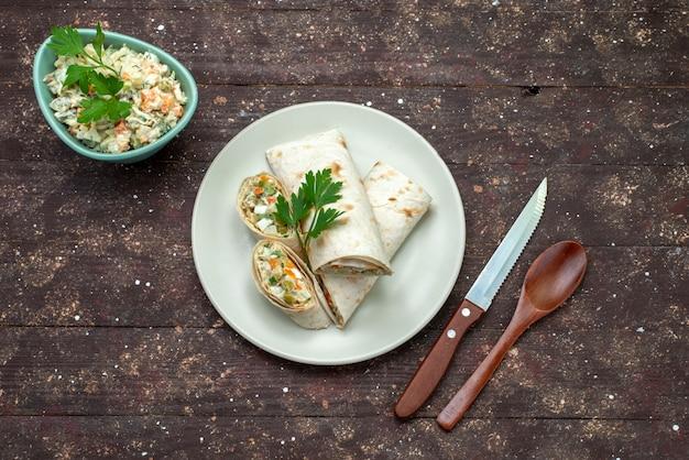Panino con vista dall'alto affettato con insalata e carne all'interno insieme a un piatto bianco di insalata maionese sul panino del pasto dello spuntino della scrivania in legno marrone
