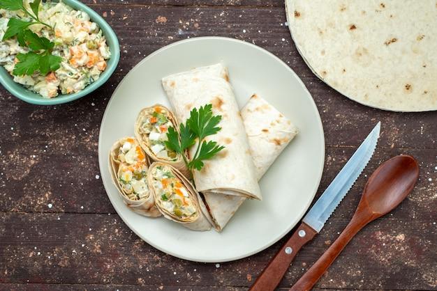 Panino con vista dall'alto affettato con insalata e carne all'interno insieme a un piatto bianco di insalata mayyonaise sul panino pasto spuntino scrivania in legno marrone