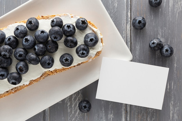 Top view sandwich with cream cheese and blueberries on plate with blank rectangle