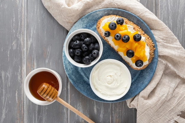 Top view sandwich  with cream cheese and fruits on plate with honey