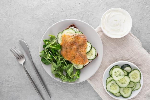 Сэндвич с огурцами и лососем на тарелке со столовыми приборами, вид сверху