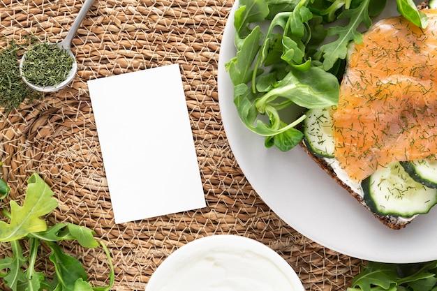 Vista dall'alto panino con cetrioli e salmone sul piatto con rettangolo vuoto