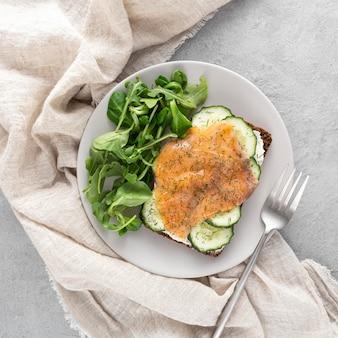 Vista dall'alto panino con cetrioli e salmone sul piatto con spinaci e forchetta