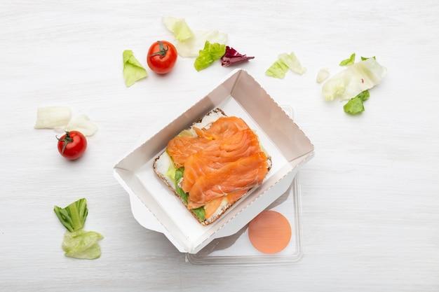 부드러운 치즈와 붉은 물고기가 들어간 상위 뷰 샌드위치는 흰색 테이블에 채소와 토마토 옆의 도시락에 있습니다. 건강한 간식의 개념.