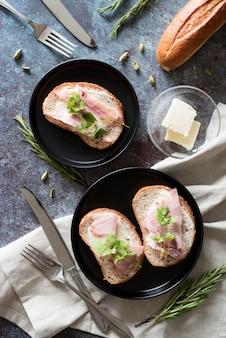Бутерброды с маслом и ветчиной на тарелке, вид сверху
