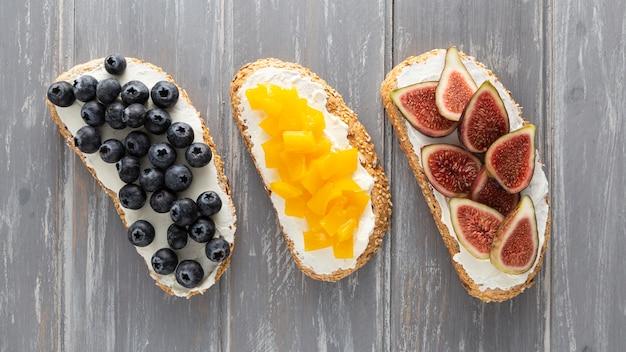 Вид сверху бутерброды со сливочным сыром и фруктами