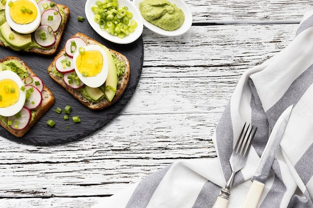 Top view of sandwiches with egg and avocado on slate