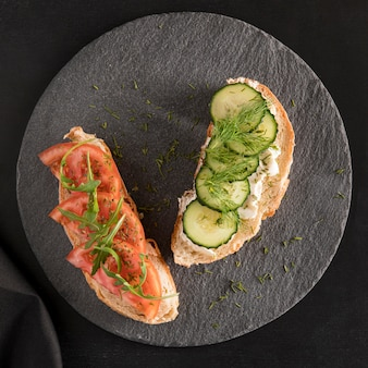Top view of sandwiches with tomatoes, cucumber and dill