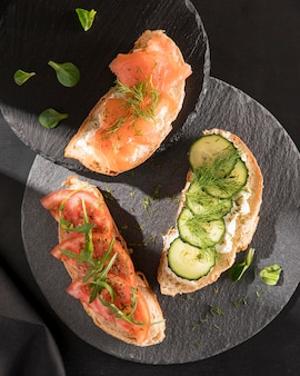 Top view of sandwiches with tomatoes, salmon and cucumber