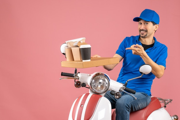 Top view of satisfied courier man wearing hat sitting on scooter on pastel peach background