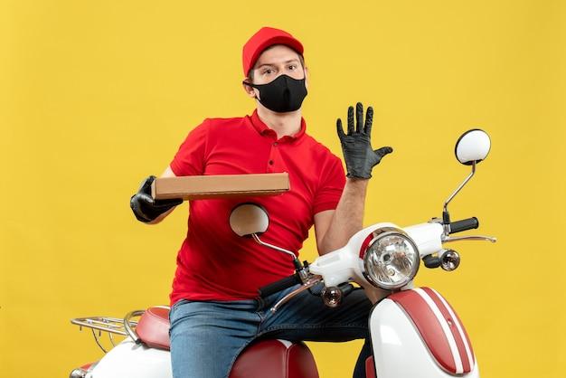 Vista superiore dell'uomo soddisfatto del corriere che indossa guanti rossi della camicetta e del cappello nella mascherina medica che si siede sullo scooter che mostra l'ordine