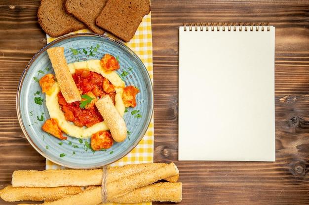 Vista dall'alto di carne condita con purè di patate e pagnotte di pane su un tavolo di legno marrone