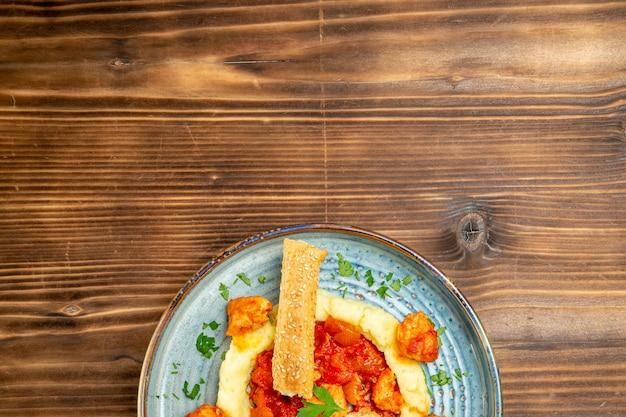 Vista dall'alto di carne condita con purè di patate e panino affettato su tavola di legno marrone