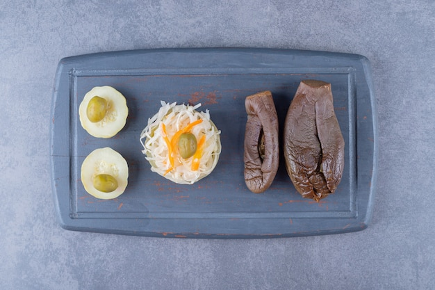 Top view of sauerkraut with filled eggplant pickle on grey wooden board.