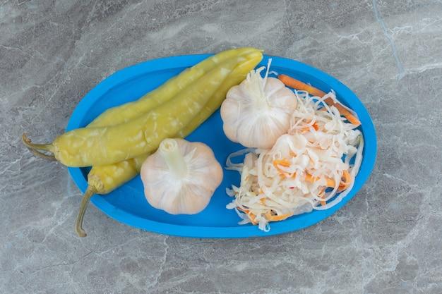 Vista dall'alto, crauti con aglio e pepe verde su piatto di legno blu.
