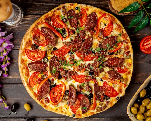 Top view of sausage pizza with tomato red bell pepper and cheese, top view