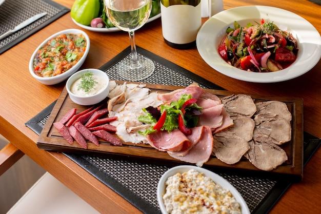 Una vista dall'alto salsicce sulla scrivania con vino bianco e verdure sulla carne del ristorante pasto cibo tavola