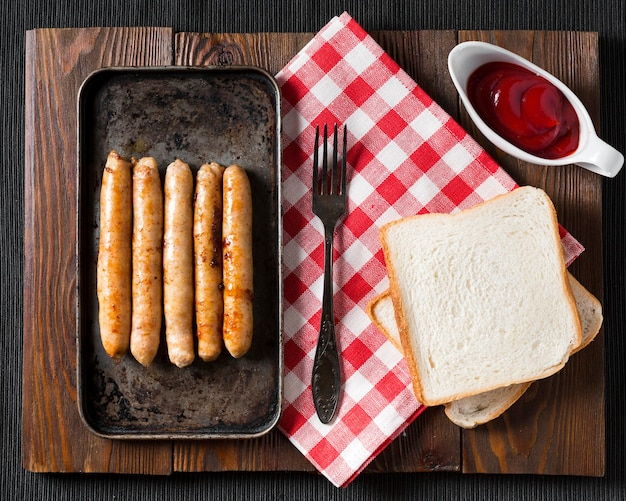 Top view sausages on tray with bread