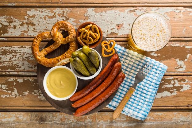 Vista dall'alto di salsicce con sottaceti e birra