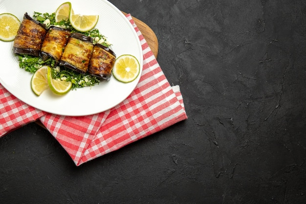 Vista dall'alto involtini salati di melanzane piatto cucinato con fette di limone su piano scuro cena cucina pasto piatto di olio di agrumi