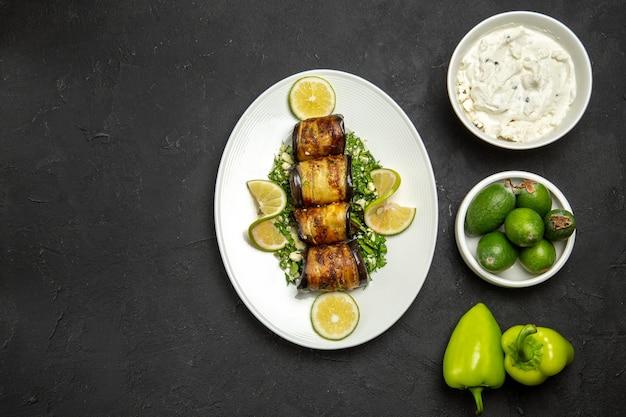 Vista dall'alto involtini salati di melanzane piatto cotto con fette di limone e feijoa sulla superficie scura cena olio pasto piatto da cucina
