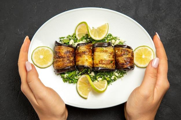 上面図おいしいナスは、暗い表面にレモンスライスが付いた調理済みの皿を巻くディナーオイル調理用食事皿