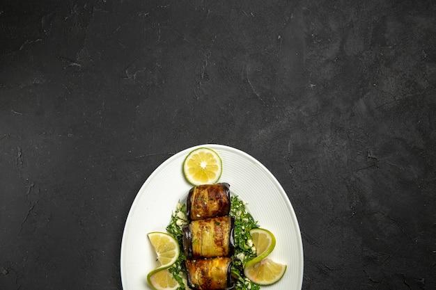 Involtini di melanzane salate vista dall'alto con fette di limone su superficie grigio scuro piatto da cucina per la cena con frutta