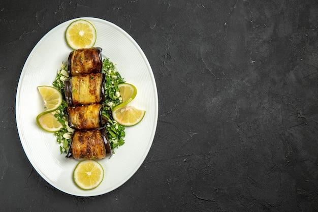 上面図暗い表面のフルーツ料理の食事の夕食の皿にレモンスライスとおいしいナスロール