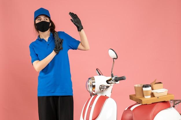 Vista dall'alto della ragazza del corriere spaventata in maschera medica in piedi accanto alla moto con una torta di caffè su di essa su sfondo color pesca pastello
