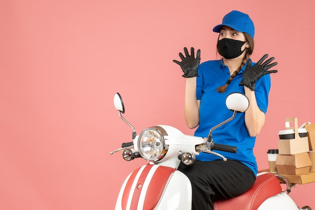 Top view of scared courier girl wearing medical mask and gloves sitting on scooter delivering orders on pastel peach background