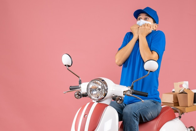 Top view of scared courier guy in medical mask wearing hat sitting on scooter delivering orders on pastel peach background