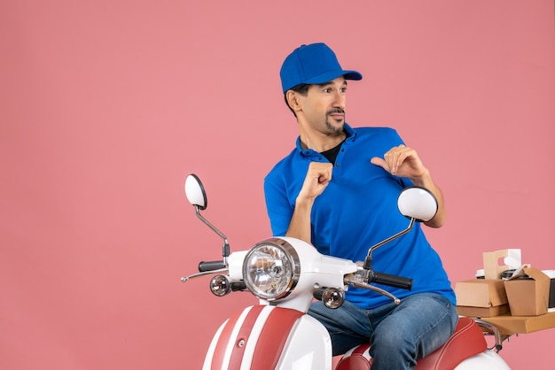 Top view of scared courier guy wearing hat sitting on scooter delivering orders on pastel peach background