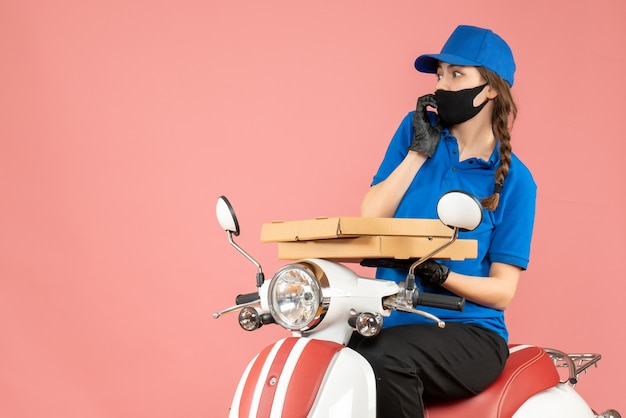 Top view of scared female courier wearing medical mask and gloves sitting on scooter delivering orders on pastel peach background