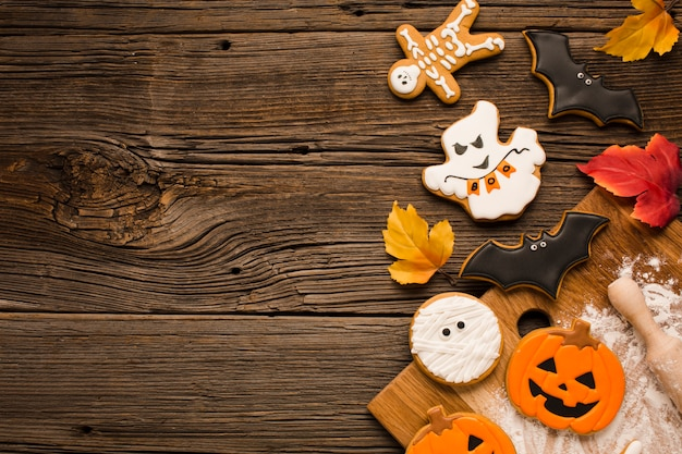 Top view scary halloween cookies on wooden background